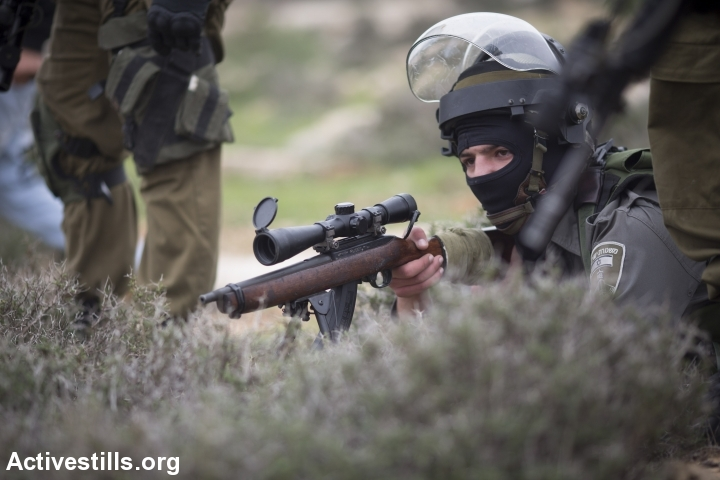 An Israeli solider with a roger riffle lies on the ground during a demonstration commemorating the death of Palestinian minister, Ziad Abu Ein, in the West Bank village of Turmus Aya, north of Ramallah, December 19, 2014. (photo: Oren Ziv/Activestills.org)