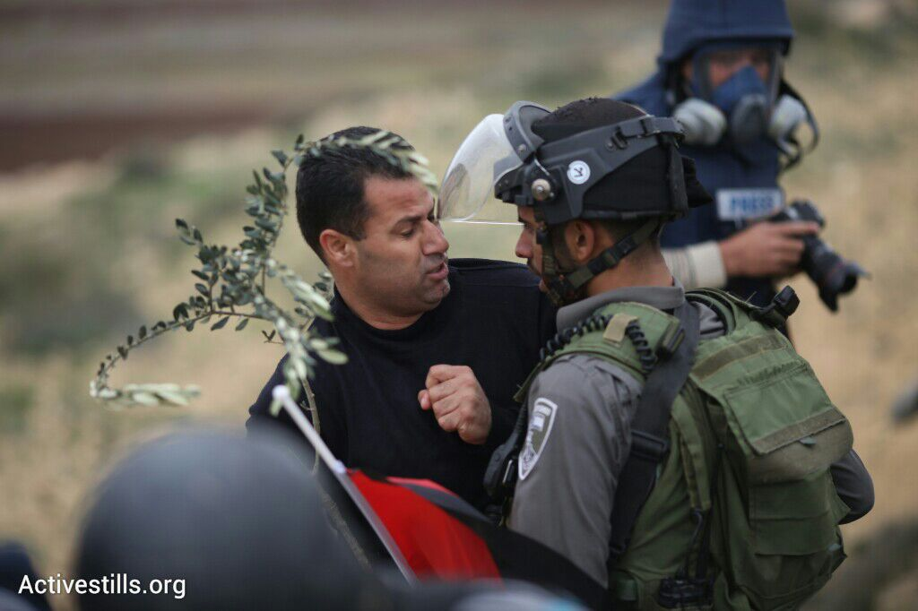 An Israeli soldier confronts a Palestinian demonstrator during the commemoration march for deceased PA Minister Ziad Abu Ein, in the West Bank village of Turmus Aya, north of Ramallah, December 19, 2014. (photo: Oren Ziv/Activestills.org)