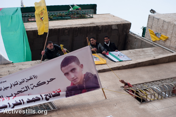 A banner picturing Salih Al-Amarin, age 15, hangs from his home in Azza Refugee Camp prior to his funeral, January 23, 2013. Al-Amarin was shot in the head by Israeli forces on January 18, 2013 during clashes in Bethlehem's nearby Aida Refugee Camp. (photo: Ryan Rodrick Beiler/Activestills.org)