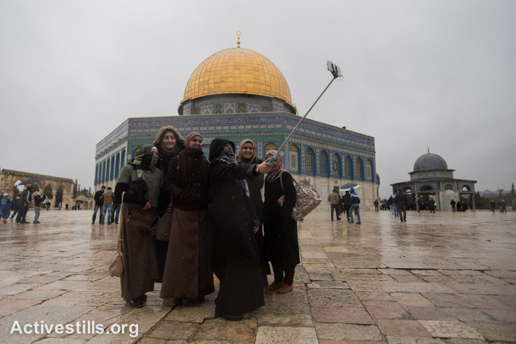 Palestinian women use their cell phone to photograph themselves outside Al Aqsa mosque in Jerusalem's old city, January 9, 2015. (photo: Activestills.org)