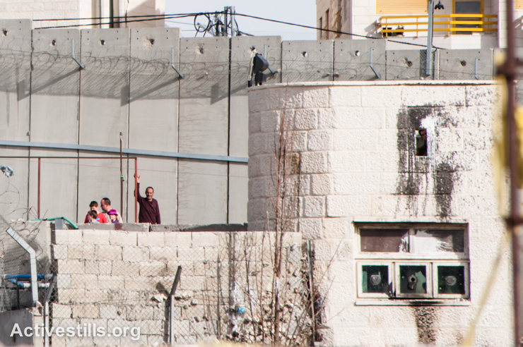 At left, visitors to Rachel's Tomb, including children, stand behind multiple layers of concrete barriers bordering Aida Refugee Camp, Bethlehem, West Bank, February 25, 2013. This photo was taken 10 minutes after an Israeli army sniper in the tower on the right shot 13-year-old Mohammad Al-Kurdi in the back with 0.22 caliber ammunition during clashes protesting the death of Arafat Jaradat, a Palestinian who died after being interrogated in Israeli custody. (photo: Ryan Rodrick Beiler/Activestills.org)