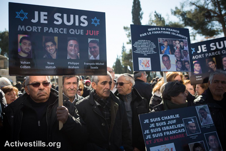 Mourners carry placards bearing portraits of the dead as they gather at a cemetery in Jerusalem during the funeral of four Jews killed in an Islamist attack on a kosher supermarket in Paris last week, January 13, 2015. Crowds of mourners attended the funeral of Yohan Cohen, Philippe Braham, Francois-Michel Saada and Yoav Hattab after their bodies were flown to Israel from France. (photo: Activestills.org)