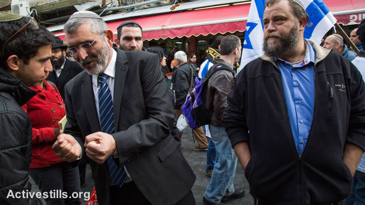 Michael Ben Ari, leader of Otzma Yehudit nationalist party is accompanied by Benzi Gopstein, head of the nationalist group Lehava, to walk in Jerusalem's Mahane Yeuda market during an election campaign, January 16, 2015.(photo: Activestills.org)