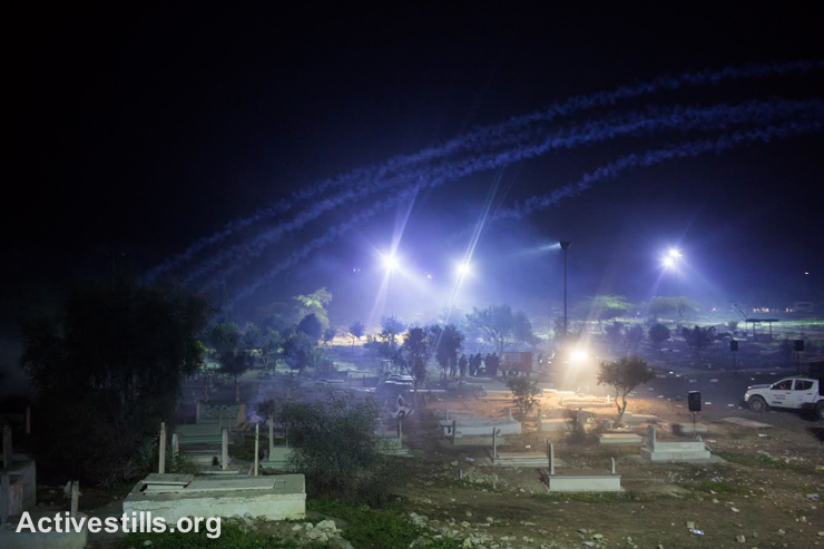 Tear gas clouds cover the cemetery of Rahat as Israeli police that burst onto the premises during the funeral of Sami al-Jaar dispersed the participants, Negev Desert, January 18, 2015. Sami al-Jaar, 22, was gunned down during a police drug raid in Rahat last week. During the clashes that followed his funeral, Sami Ziadna, 42, suffocated to death from tear gas inhalation and twenty-two participants were injured. Southern district police commander admitted there was an agreement that no policemen were allowed to enter the cemetery during the funeral. (photo: Activestills.org)