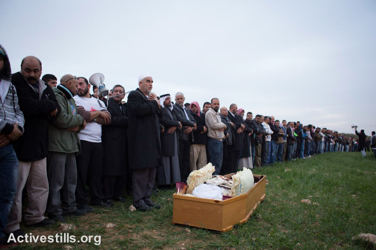 Bedouins pray near the body of Sami Ziadna, 42, during his funeral in the southern Bedouin city of Rahat, on January 19, 2015. Sami Zayadna was killed during clashes that erupted when a police car burst into the area where the funeral of Sami al-Jaar was held. Sami al-Jaar, 22, was gunned down during a police drug raid in Rahat the day before. (photo: Activestills.org)
