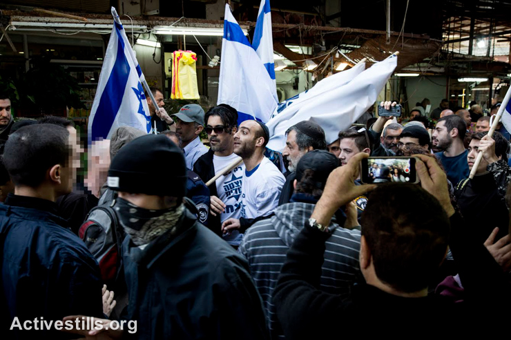 Right-wing activists taking part in the election campaign of Otzma Yehudit political party are countered by left-wing activists that came to protest the party's fascist and racist agenda, Tel-Aviv's Ha'Carmel market, January 23, 2015. Police pushed away the anti-fascist activists, separating between the two groups, allowing the right-wing activists to continue on their march. (photo: Activestills.org)