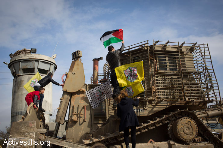 Protesters place Fatah and Palestinian flags on an Israeli army D9 bulldozer of the during the weekly protest against the occupation in the West Bank village of Nabi Saleh, January 2, 2015. (Photo by Oren Ziv/Activestills.org)
