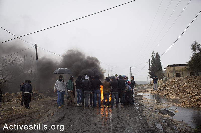 Palestinian youth stand around a burning tire during the weekly protest against the occupation in the West Bank village of Kfar Qaddum, January 9, 2015. Activestills.org