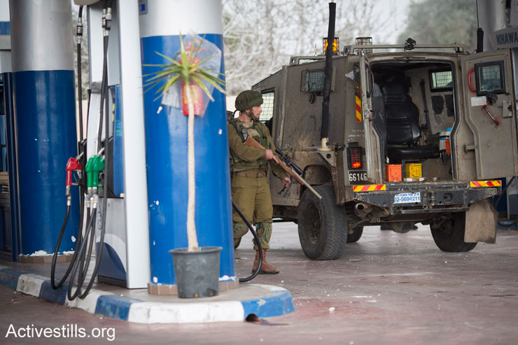 An Israeli army sharp-shooter stands guard in a gas station during the weekly protest against the occupation in the West Bank village of Nabi Saleh, January 2, 2015. (Photo by Oren Ziv/Activestills.org)