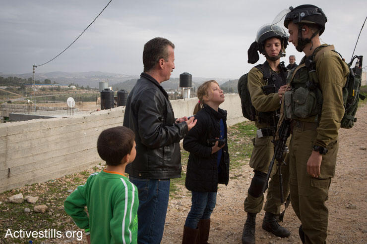 Palestinian children argue with Israeli soldiers during the weekly protest against the occupation in the West Bank village of Nabi Saleh, January 2, 2015. (Photo by Oren Ziv/Activestills.org)