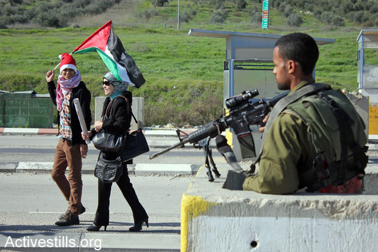 Palestinian activists protest against the Israeli occupation at the Huwwara military checkpoint, south of Nablus, January 1, 2015. (Photo by Ahmad Al-Bazz/Activestills.org)