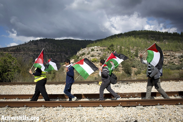 Palestinians march on the railway line connecting Tel Aviv and Jerusalem through the West Bank, during a protest against the plan to build the separation wall in the West Bank village of Battir, November 13, 2012. (Photo by Oren Ziv/Activestills.org)