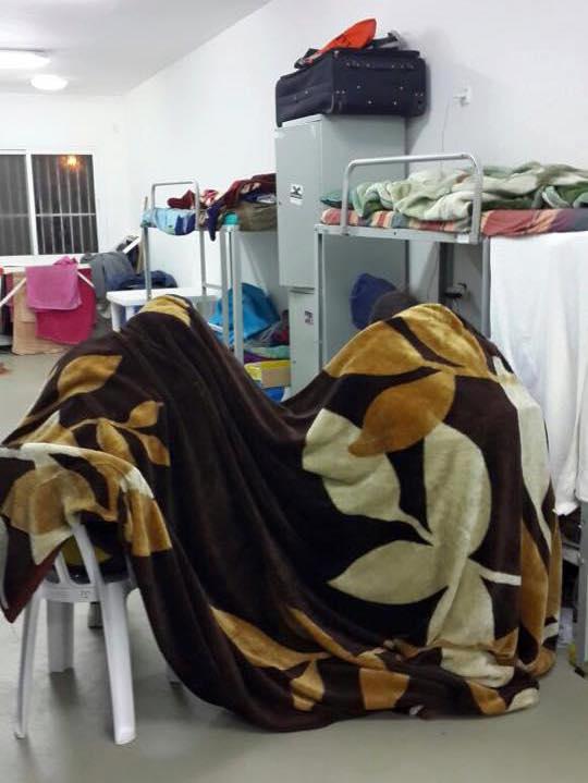 An asylum seeker lies under blanket inside a room at Holot, December 10, 2015. (Photo by an anonymous asylum seeker, courtesy of Mothers Against Holot)
