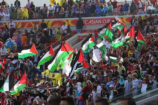 Palestine fans wave flags during their first game against Japan in the Asian Cup. (photo: Nasya Bahfen CC BY-ND 2.0)