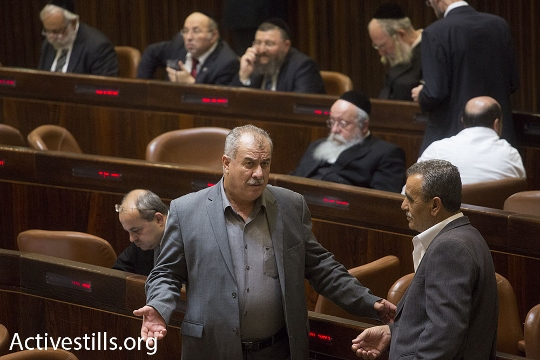 Hadash MK Mohammad Barakeh (left) speaks to Balad MK Jamal Zahalka in the Knesset chambers. (photo: Activestills)