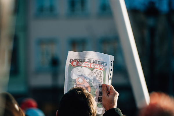 People holding Charlie Hebdo cover with Mohammed cartoon during a unity rally (Marche Republicaine), in which 50000 people paid tribute following the three-day killing spree in Paris, January 11, 2015. (Photo by Shutterstock.com/Hadrian)