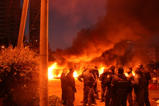 Police next to the burning barricades, Givat Amal, Tel Aviv, December 29, 2014. (Photo by Haggai Matar)