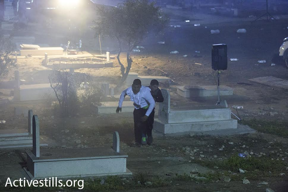 Bedouin men dodge live bullets and tear gas during clashes that erupted in the wake of a funeral, Rahat, southern Israel, January 18, 2015. (photo: Oren Ziv/Activestills.org)