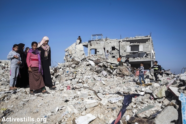 Relatives walk amidst the rubble of the home of Zaki Wahdan in the city of Beit Hanoun, northern Gaza City, November 10, 2014. Eight members of the Wahdan family, mostly women and children were killed. (Photo by Anne Paq/Activestills.org)