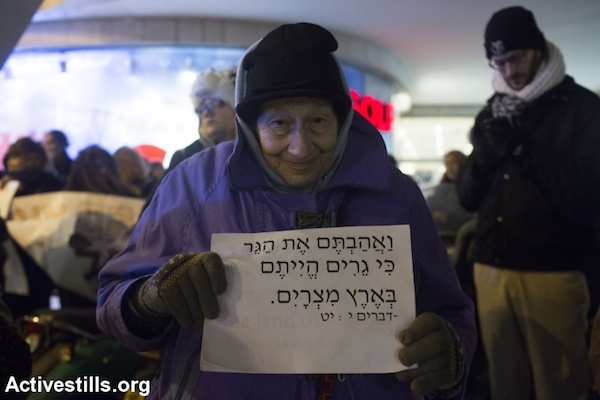 """An activist with """"Mothers Against Holot"""" holds a sign reading quoting from the biblical passage, """"And you shall love [the strangers] as yourself; for you were strangers in the land of Egypt,"""" January 10, 2015, Tel Aviv. (Photo by Oren Ziv/Activestills.org)"""