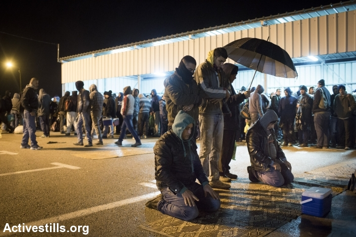 Palestinian workers pray after crossing the Eyal checkpoint, between the West Bank city of Qalqilya and Israel, January 4, 2015. (photo: Oren Ziv/Activestills.org)