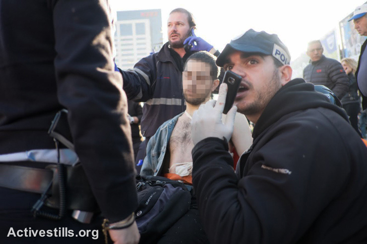 Israeli medics treat a Palestinian man on a gurney after he stabbed and wounded at least 10 passengers in an attack on a bus in Tel Aviv, January 21, 2015. The attacker struck in the morning rush hour in the center of Israel's commercial capital before being shot by a passing prison service officer. (photo: Activestills.org) Read more here.
