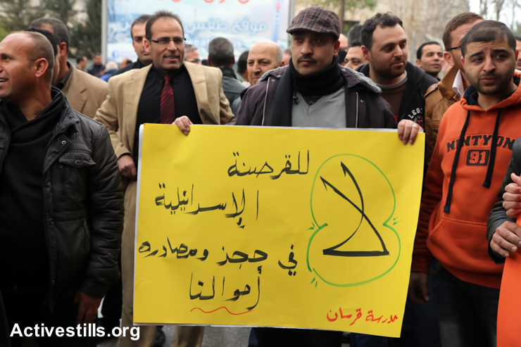 """A Palestinian teacher holds a sign that reads: """"Freezing our money is an Israeli piracy"""", during a protest in front of the Ministry of Education in the West Bank city of Nablus, February 8, 2015. On January 3, Israeli authorities froze the transfer of tax funds collected by Israel for the Palestinian Authority in response to Mahmoud Abbas' move to call on the ICC to pursue war-crimes charges against Israel. PA salaries are estimated to total some $200 million per month, $120 million of which is covered from the taxes collected by Israel. (photo: Ahmad Al-Bazz/Activestills.org)"""