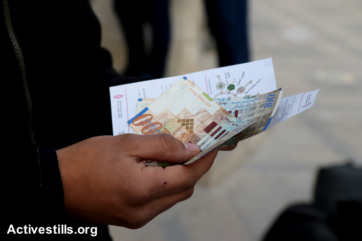 A Palestinian public-sector workers holds part of his salary withdrawn from an ATM, Nablus, West Bank, February 9, 2015. (photo: Ahmad Al-Bazz/Activestills.org)