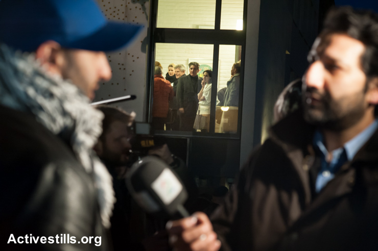 "Members of the Oslo Jewish community watch from inside their synagogue as Ali Chishti, one of the organizers of the ""Ring of Peace vigil is interviewed by media, February 21, 2015. The vigil was organized by Muslim youth in solidarity with Norway's Jewish community following anti-Jewish attacks in Denmark and other parts of Europe."