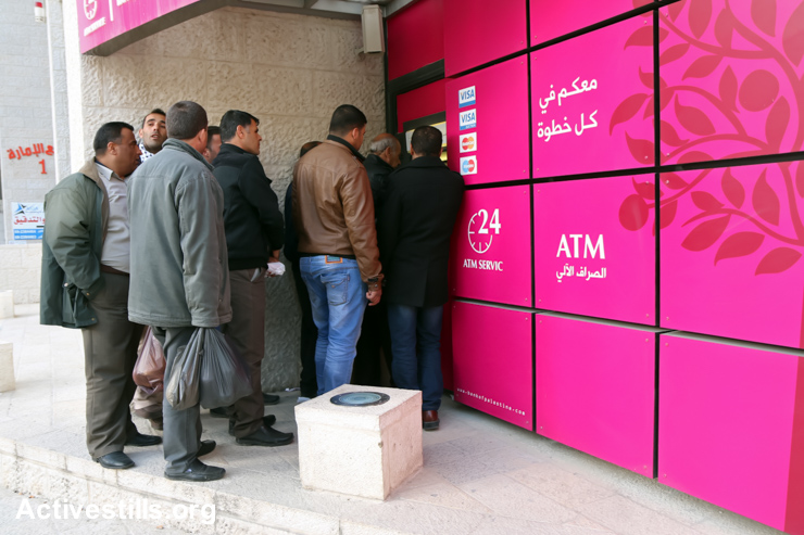 Palestinian public-sector workers stand in queue for their salaries in Nablus, West Bank, February 9, 2015. Monday, the PA announced it will pay only 60% of January's salaries. (photo: Ahmad Al-Bazz/Activestills.org)