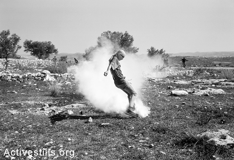 A Palestinian youth kicks a tear gas canister during a protest against the Wall, 2014. Miki Kratszman / Activestills.org