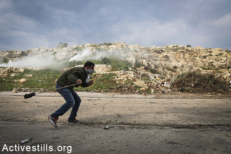 A Palestinian from the West Bank village of Azzun throwing back a tear gas canister, during a protest for the opening of the eastern gate to the village, which has been closed by Israel since 1990, February 14, 2015. Ahmad al-Bazz/Activestills.org