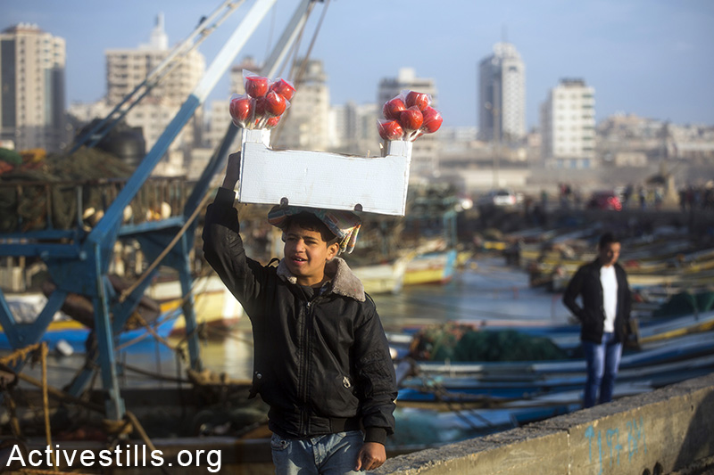 A Palestinian child sells sweets in the harbour of Gaza city, February 13, 2015. Anne Paq / Activestills.org