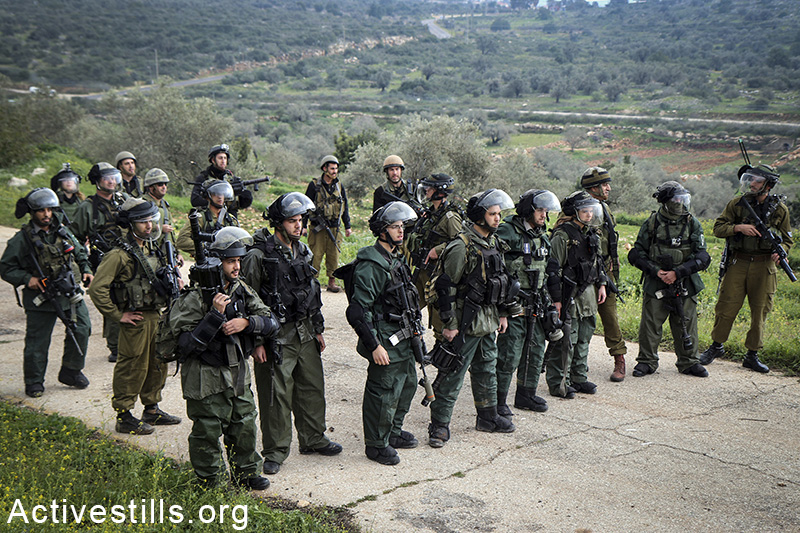 Israeli soldiers block a main road in the village of Azzun, during a protest for the opening of the eastern gate to the village, which has been closed by Israel since 1990, West Bank, February 14, 2015. Ahmad al-Bazz / Activestills.org