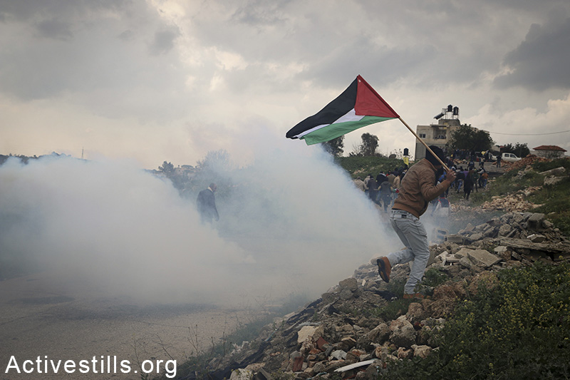 A Palestinian from the West Bank village of Azzun runs from tear gas during a protest calling for the opening of the eastern gate to the village, which has been closed by Israel since 1990, February 14, 2015. Ahmad al-Bazz / Activestills.org