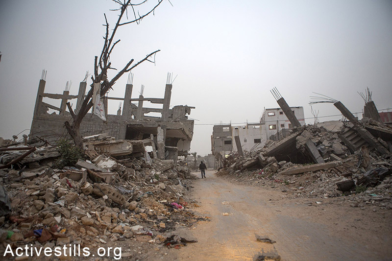 A Palestinian walks during a storm in one of the destroyed quarter of Shujayea, east of Gaza city, February 11, 2015. Anne Paq / Activestills.org