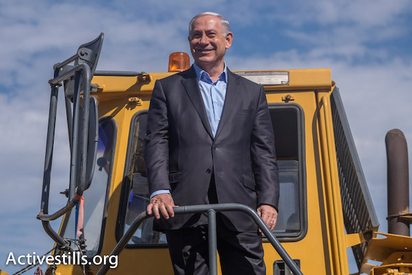 Prime Minister Benjamin Netanyahu stands on a tractor at the West Bank settlement of Eli at a campaign event, February 11, 2015. (Photo by Activestills.org)