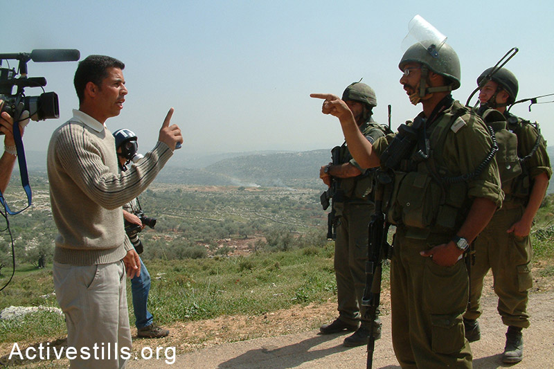 Muhammed Khatib speaks to Israeli soldiers during an action against the construction of the Wall, Bil'in, West Bank, 2005. Oren Ziv / Activestills.org