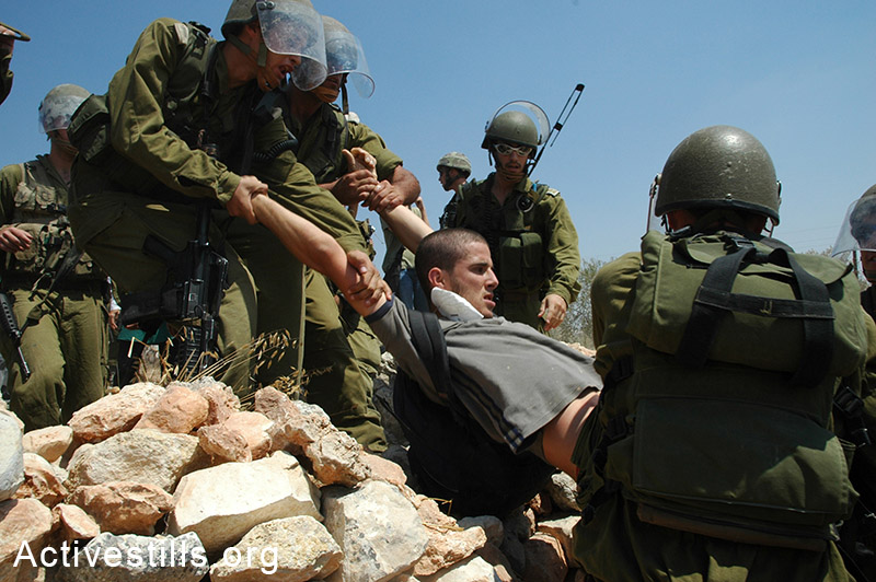 The Israeli activist, Ben Ronen, being arrested by the army during the weekly protest against the building of the Wall in the West Bank village of Bil'in, August 26, 2005. Yotam Ronen / Activestills.org