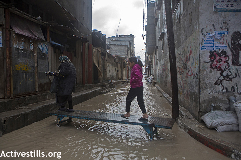 A Palestinian woman and girl use a makeshift bridge to cross a flooded street during the winter storm in Al Shati Refugee Camp, Gaza City, February 19, 2015. (Ann Paq/Activestills.org) The poor infrastructure in Gaza resulted in flooding in the streets and sewage overflow. Bad weather conditions especially affected the tens of thousands of Palestinians who lost their homes during last summer's Israeli offensive, during which 18,000 housing units were destroyed. Many of them remain in shelters or in their damaged homes.