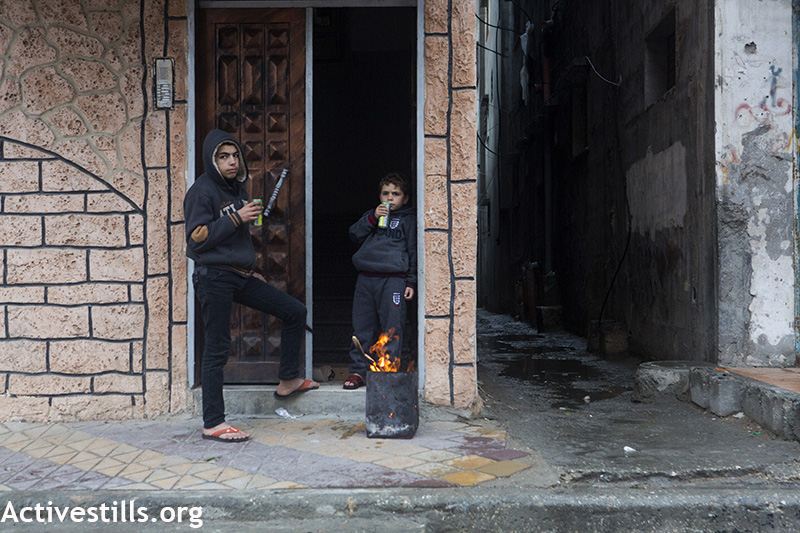 Palestinian children warm themselves around a fire during THE winter storm in Al Shati Refugee Camp, Gaza City, February 19, 2015. (Photo by Ann Paq/Activestills.org)