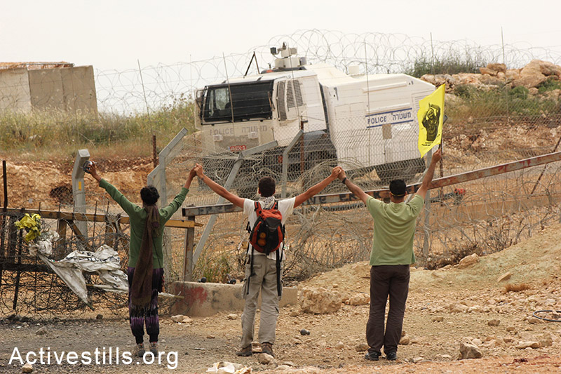 International activists confront an Israeli skunk canon during a protest in Bil'in, West Bank, 2001. Ahmad al-Bazz / Activestills.org