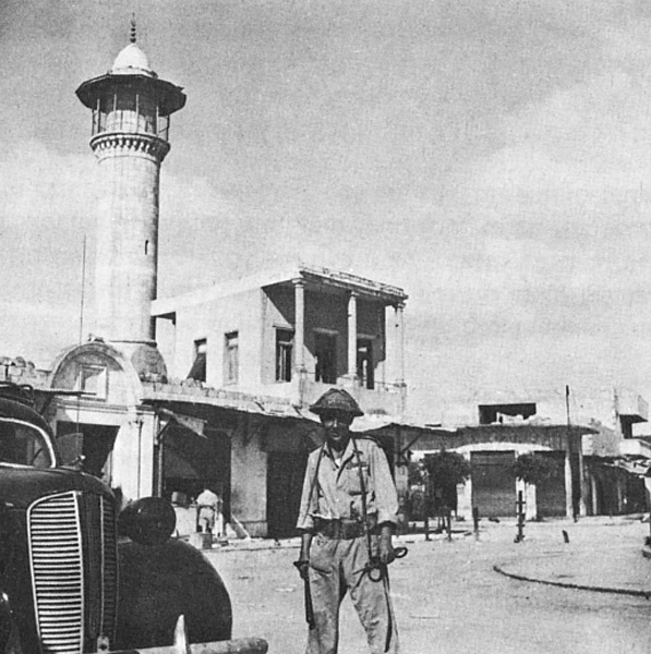 An Israeli soldier stands outside the Dahmash mosque in central Lydd.