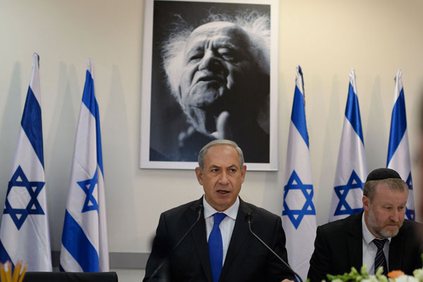 Prime Minister Benjamin Netanyahu stands in front of a portrait of Israel's first prime minister, David Ben-Gurion. (Kobi Gideon/GPO)