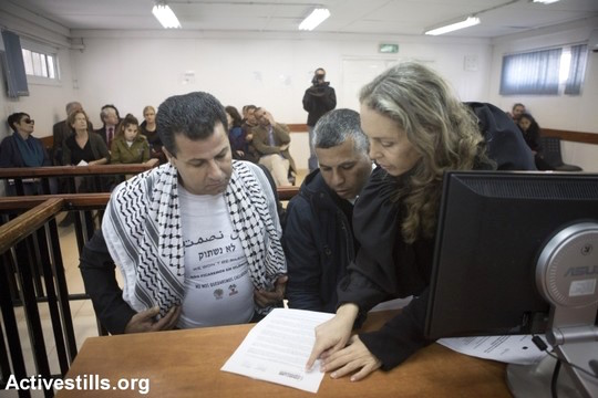 Abdullah Abu Rahmah (left) in Ofer Military Court with his attorneys, Gaby Lasky and Muhammad Khatib, February 8, 2015. (Photo by Oren Ziv/Activestills.org)