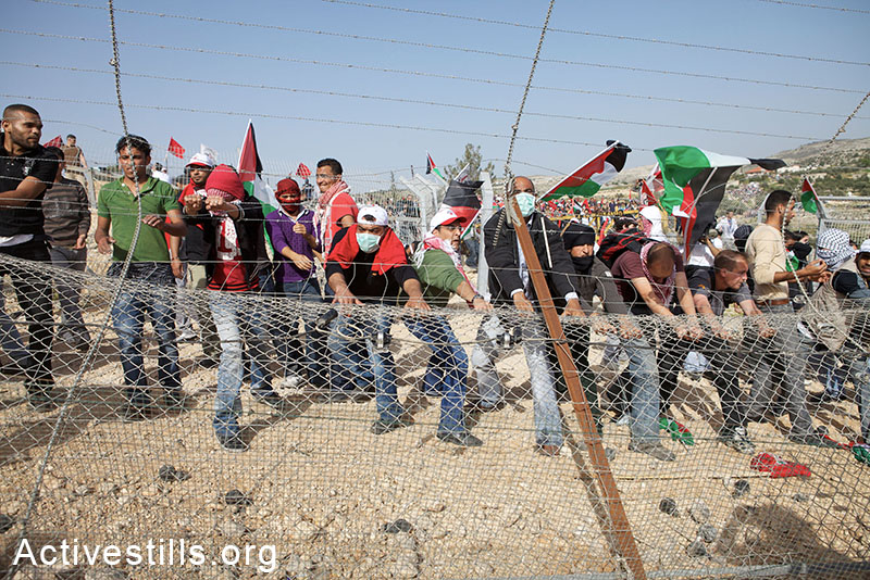 Demonstrators dismantle a section of the barrier during a demonstration marking the fifth anniversary of the struggle against the Israeli barrier in the West Bank village of Bil'in, Friday, 19, 2010. By: Anne Paq / Activestills.org