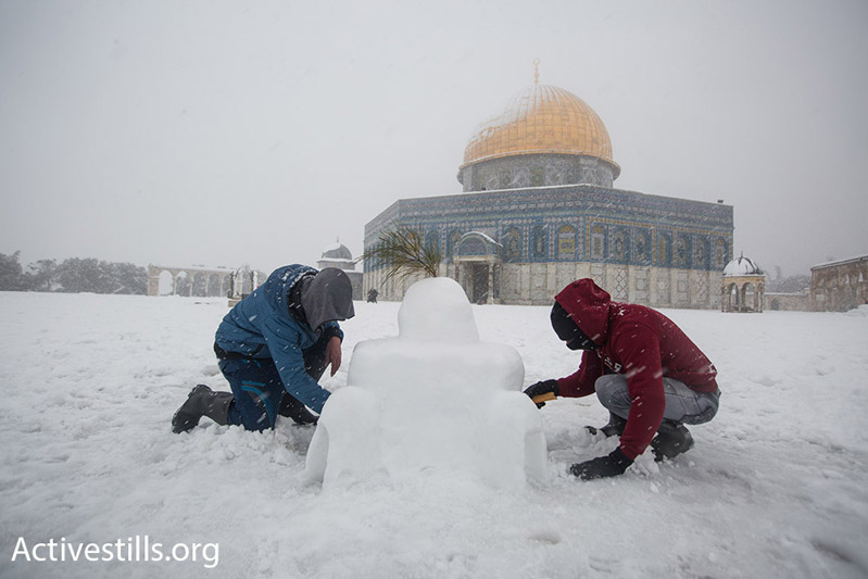 Palestinian children make a snow model of the Dome of the Rock in front on Al Aqsa Mosque compound, February 20, 2015. (Photo by Faiz Abu Rmeleh/Activestills.org)