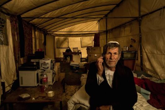 A man sits in his tent at the Arlozorov encampment in Tel Aviv. (Photo by Dan Haimovich)