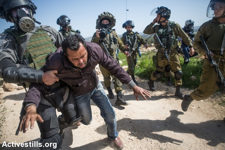 An Israeli Border Policeman arrests a Palestinian activist during a protest marking ten years of popular struggle against the wall in the West Bank village Bil'in, February 27, 2015. (photo: Yotam Ronen/Activestills.org)