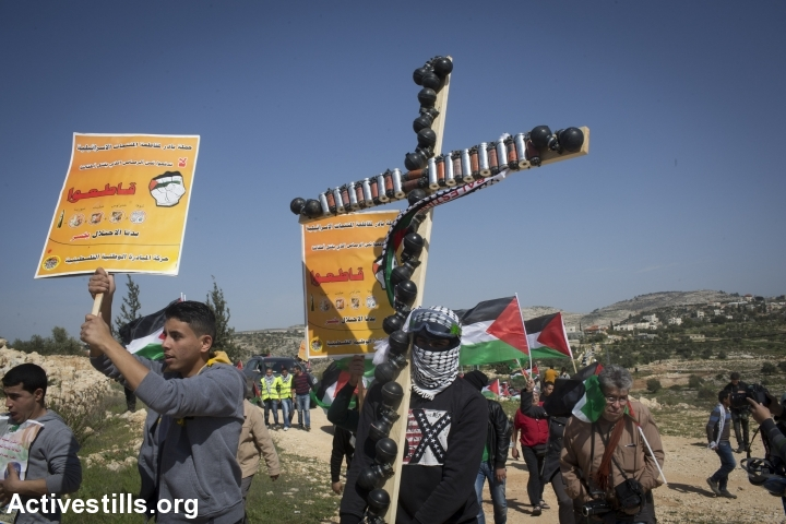 A Palestinian protester holds up a cross decorated with spent tear gas canisters during a demonstration marking 10 years of struggle in Bil'in. (photo: Yotam Ronen/Activestills.org)